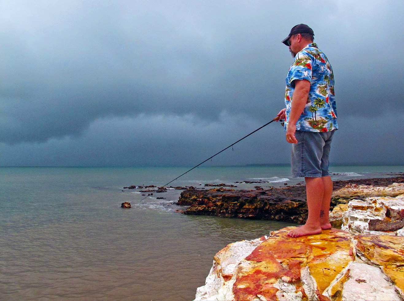 Starlo fishes from the rocks at East Point under a rather ominous Wet Season sky.